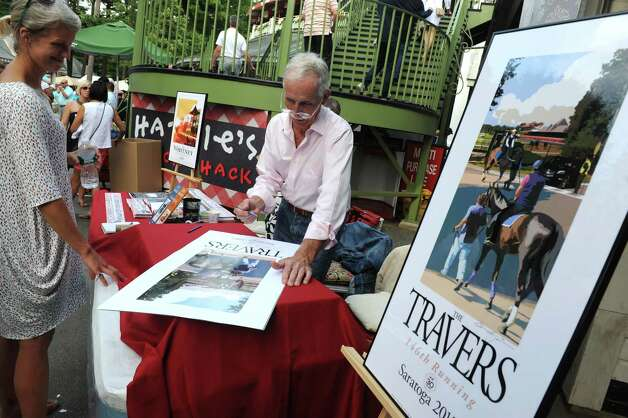 Artist Gregory Montgomery sign prints of his 2015 Travers poster on Travers race day at Saratoga Race Course on Saturday Aug. 29, 2015 in Saratoga Springs, N.Y.  (Michael P. Farrell/Times Union) Photo: Michael P. Farrell / 00033156A