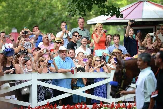 Spectators gather to view American Pharoah, right, in the paddock before the start of the Travers Stakes at Saratoga Race Course Saturday afternoon, Aug. 29, 2015, in Saratoga Springs, N.Y. Keen Ice with Javier Castellano was the winner. (Will Waldron/Times Union) Photo: WW / 00033155B