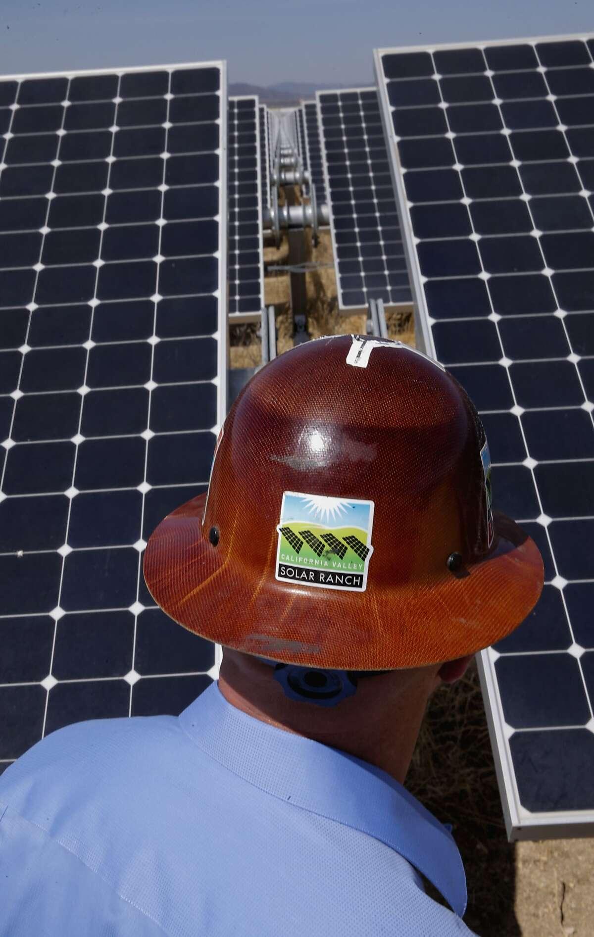SunPower's west coast operations leader Lance Long walks past a row of solar panels at the California Valley Solar Farm near Santa Margarita, Calif., in San Luis Obispo County, on Fri. August 28, 2015.