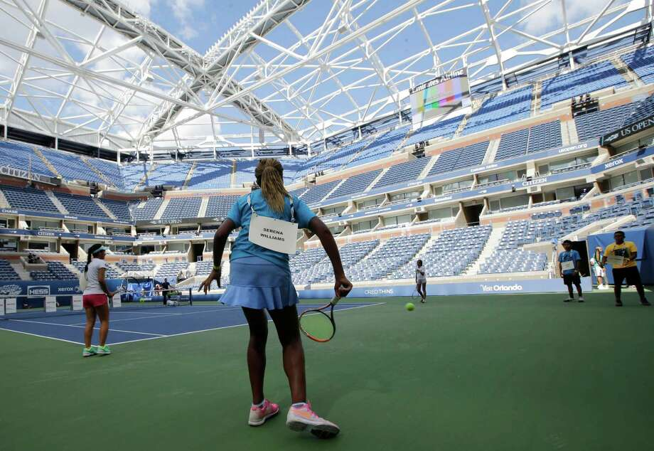Standing in for Roger Federer and Serena Williams, Nicole Massa, left, and Khadia Ba, center, warm up on Arthur Ashe court during a rehearsal for Arthur Ashe Kids' Day at the USTA Billie Jean King National Tennis Center in New York, Thursday, Aug. 27, 2015.  The framework for a partially-complete retractable roof, above, provides shade for fans, but rain delays could still plague the U.S. Open, a two-week long tennis tournament.  (AP Photo/Kathy Willens) ORG XMIT: NYKW204 Photo: Kathy Willens / AP