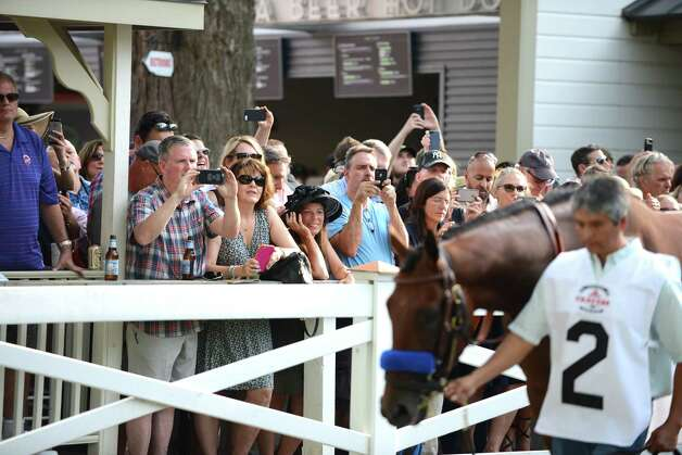 Spectators gather at the paddock rail to view American Pharoah, right, before the start of the Travers Stakes at Saratoga Race Course Saturday afternoon, Aug. 29, 2015, in Saratoga Springs, N.Y. Keen Ice with Javier Castellano was the winner. (Will Waldron/Times Union) Photo: WW / 00033155B
