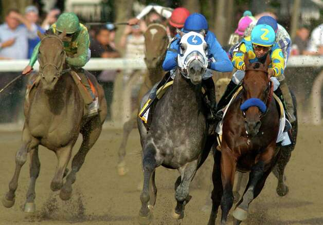 Keen Ice with jockey Javier Castellano, left overtakes American Pharoah with jockey Victor Espinoza, right and Frosted with jockey Jose Lezcano, center  to win the 146th running of the Travers Stakes Saturday evening Aug. 29, 2015 at the Saratoga Race Course in Saratoga Springs, N.Y.    (Skip Dickstein/Times Union) Photo: SKIP DICKSTEIN / 00033110A