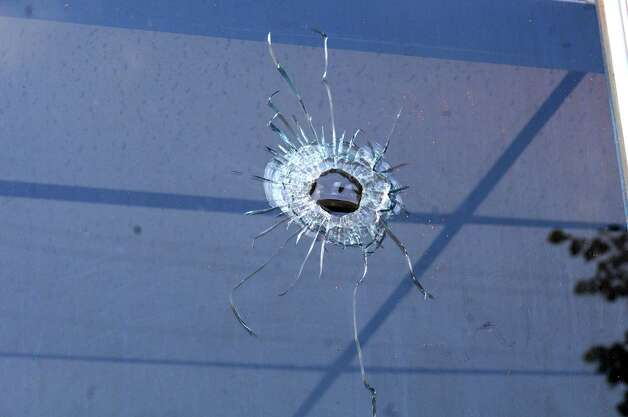 A bullet hole is seen in the window of a store on the corner of 112th St. and Fifth Ave. on Tuesday, Aug. 25, 2015 in Lansingburgh, N.Y. A shoot-out between Troy police officers, Joshua Comitale and Chad Klein and 39-year-old Thaddeus Faison of Albany took place Saturday night. Faison was shot repeatedly near the intersection of 112th Street and Fifth Avenue by at least one of the officers and was later pronounced dead at St. Mary's Hospital. (Lori Van Buren / Times Union) ORG XMIT: MER2015082910334003 Photo: Lori Van Buren / 00033124A