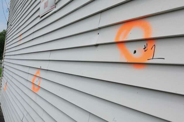 Bullet holes are seen in the siding of a building behind Jimmy's Pizzeria on Tuesday, Aug. 25, 2015 in Lansingburgh, N.Y. The bullet hole is from a shoot-out between Troy police officers, Joshua Comitale and Chad Klein and 39-year-old Thaddeus Faison of Albany. Faison was shot repeatedly near the intersection of 112th Street and Fifth Avenue by at least one of the officers and was later pronounced dead at St. Mary's Hospital.(Lori Van Buren / Times Union) ORG XMIT: MER2015082910335604 Photo: Lori Van Buren / 00033124A