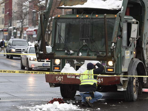 An Albany police forensics investigator photographs the front of a garbage truck involved in the crash that killed Ashiqur Rahman at the intersection of Quail Street and Central Avenue Thursday morning, Feb. 12, 2015, in Albany, N.Y. (Skip Dickstein/Times Union archive) ORG XMIT: MER2015041315114083 Photo: SKIP DICKSTEIN