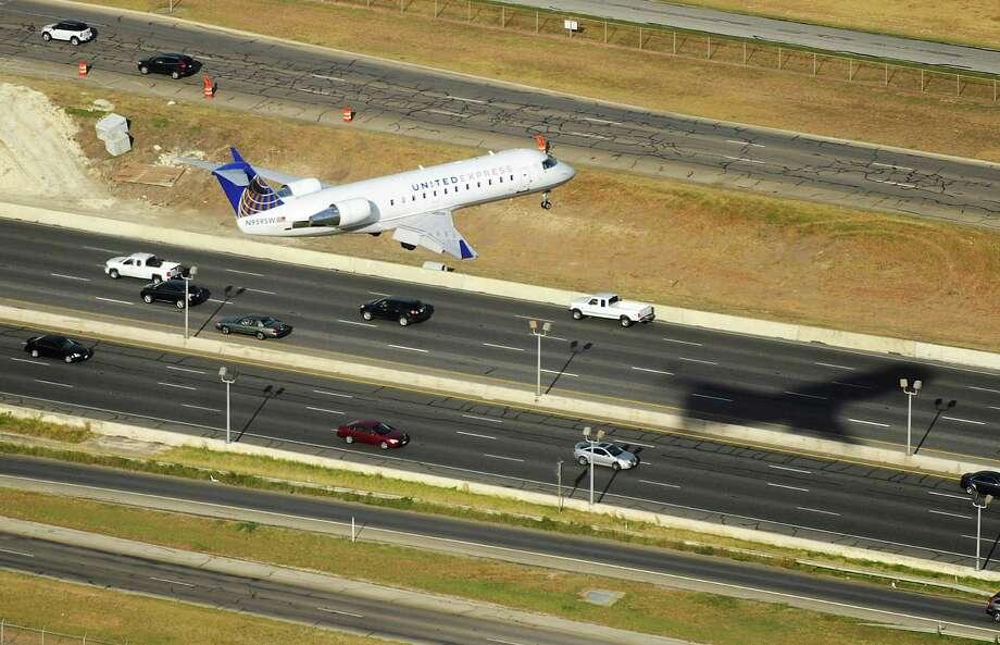 A United Airlines jetliner flies over U.S. 281 near International Airport. Photo: Billy Calzada /San Antonio Express-News / San Antonio Express-News