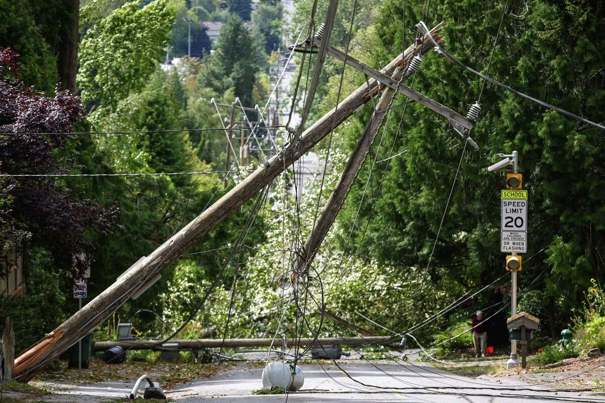 A block-long length of power lines and poles are shown in Lake City after they were knocked down during a windstorm that caused damage across the Pacific Northwest.