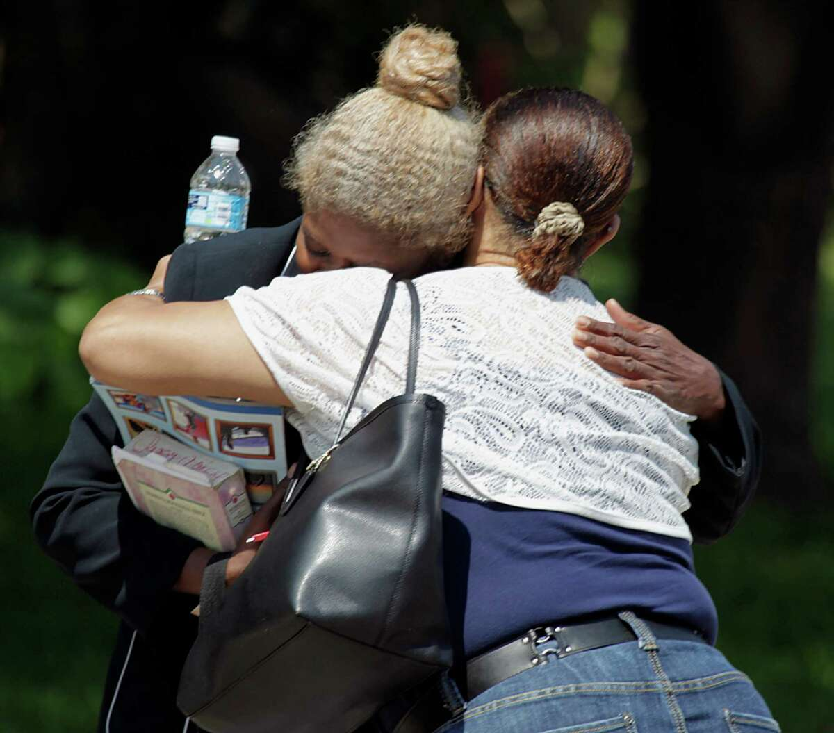 A woman believed to be the mother of the suspect in the shooting death of Harris County Deputy Darren Goforth is hugged by another woman near the suspect's home in Cypress.