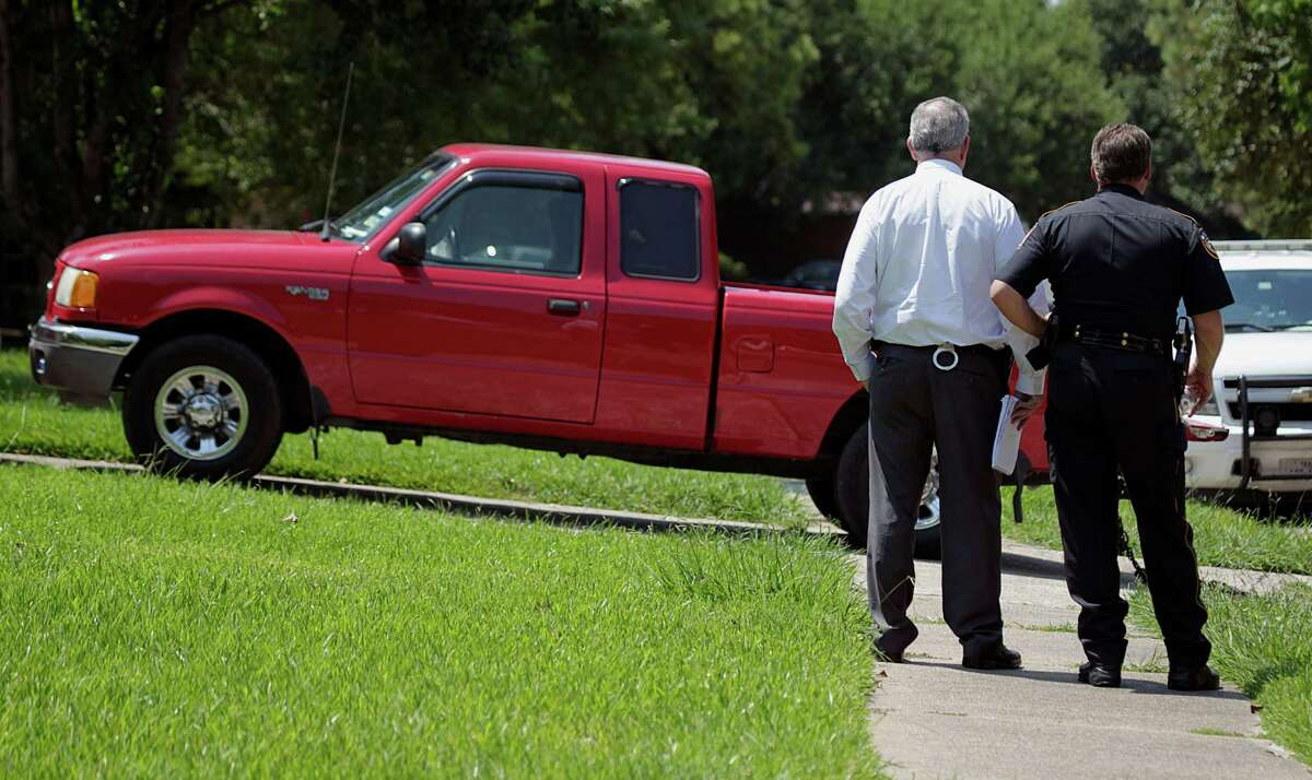 A Harris County Sheriff Department detective and a deputy wait for a the truck to be towed for processing at the home of a suspect in the shooting death of a Harris County Sheriff Department Deputy Saturday, Aug. 29, 2015, in Houston. ( James Nielsen / Houston Chronicle )