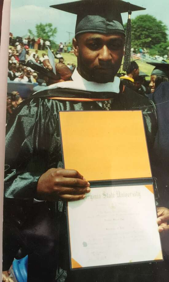 "Donald ""Dontay"" Ivy holds up his degree after graduating from Virginia State Univeristy. (Family photograph)"
