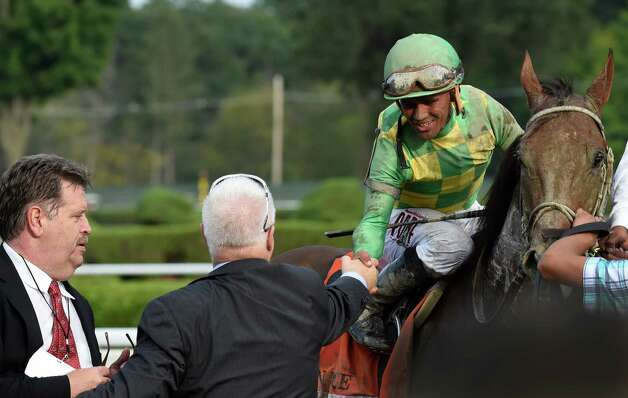 Jockey Javier Castellano is congratulated by Donegal Racing's Jerry Crawford, center, and trainer Dale Roman's, left  after winning the 146th running of the Travers Stakes Saturday evening Aug. 29, 2015 at the Saratoga Race Course in Saratoga Springs, N.Y.    (Skip Dickstein/Times Union) Photo: SKIP DICKSTEIN / 00033110A