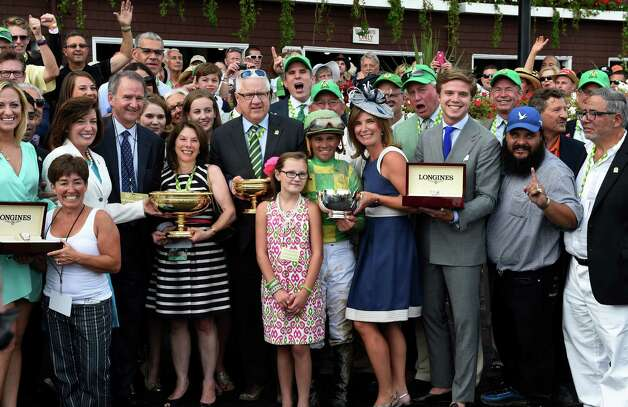 Donegal Racing's managing partner Jerry Crawford, center receives the winner's trophy from NYRA CEO Chris Kay, third from left, after his charge, Keen Ice won the 146th running of the Travers Stakes Saturday evening Aug. 29, 2015 at the Saratoga Race Course in Saratoga Springs, N.Y.    (Skip Dickstein/Times Union) Photo: SKIP DICKSTEIN / 00033110A