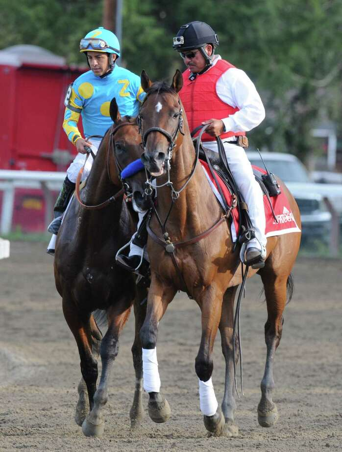 Victor Espinoza, left, rides American Pharoah back to the finish line after losing to Keen Ice with Javier Castellano in the Travers Stakes at Saratoga Race Course Saturday afternoon, Aug. 29, 2015, in Saratoga Springs, N.Y. (Will Waldron/Times Union) Photo: WW / 00033155B