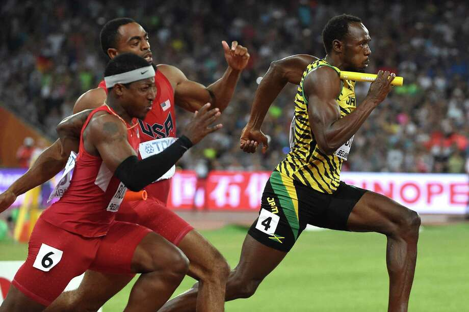 Usain Bolt, right, begins the anchor leg of Jamaica's gold-medal-winning 4X100 relay while a botched handoff between Mike Rodgers, left, and Tyson Gay earned the Americans a disqualification Saturday. Photo: WANG ZHAO, Stringer / AFP or licensors