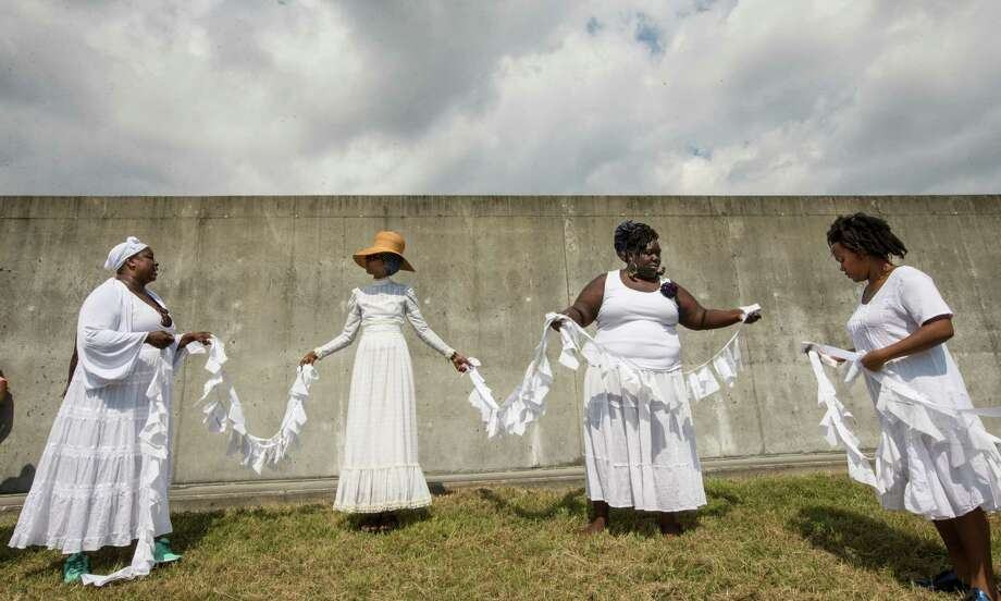 Women from Ecohybridity perform a healing ceremony on Saturday by the Industrial Canal levee in the Lower 9th Ward, which was breached 10 years ago after Hurricane Katrina hit New Orleans. Small flags attached to a string represent the more than 1,800 lives lost as a result of the disastrous storm. Photo: Brett Coomer, Staff / © 2015 Houston Chronicle