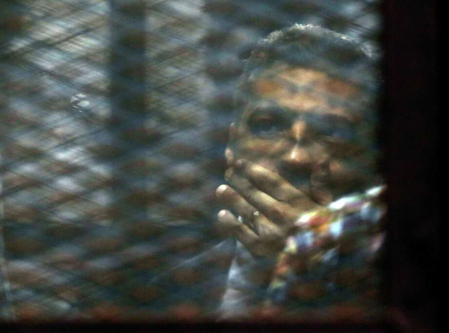 Canadian Al-Jazeera journalist Mohammed Fahmy listens to his verdict from a soundproof glass cage Saturday inside Tora prison in Cairo, Egypt. Photo: Amr Nabil, STF / AP