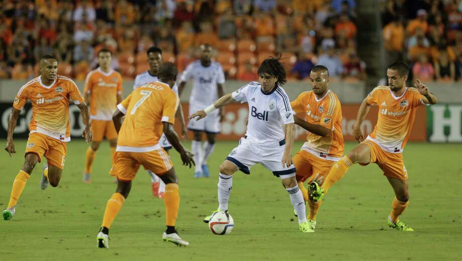 Vancouver FC midfielder Mauro Rosales (7) is met by Houston Dynamo defender/midfielder DaMarcus Beasley (7) as he pressured by midfielder Alex (14) and defender Raul Rodriguez (5) during a soccer game Saturday, Aug. 29, 2015, in Houston. (AP Photo/Bob Levey) Photo: Bob Levey, Associated Press / FR156786 AP
