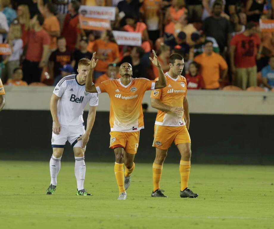 Dynamo midfielder Ricardo Clark (13) celebrates with forward Will Bruin (12) as Whitecaps FC defender Tim Parker (26) looks on after Clark opened the scoring in the first half Saturday night. Photo: Bob Levey, Associated Press / FR156786 AP