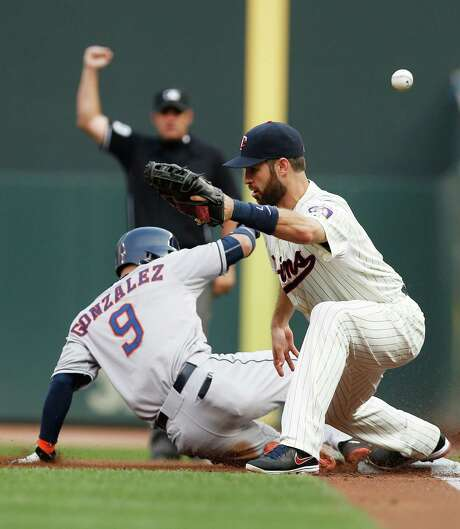 First-base umpire Mark Ripperger, rear, makes an early out call on a double-play try, but the Astros' Marwin Gonzalez winds up safe at first when the Twins' Joe Mauer can't handle the throw in the first inning. Photo: Jim Mone, STF / AP