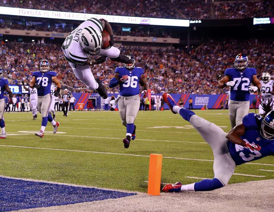 EAST RUTHERFORD, NJ - AUGUST 29:  Zac Stacy #38 of the New York Jets jumps over  Brandon Meriweather #43 of the New York Giants to score a touchdown in the second quarter during preseason action at MetLife Stadium on August 29, 2015 in East Rutherford, New Jersey.  (Photo by Elsa/Getty Images) ORG XMIT: 564375227 Photo: Elsa / 2015 Getty Images