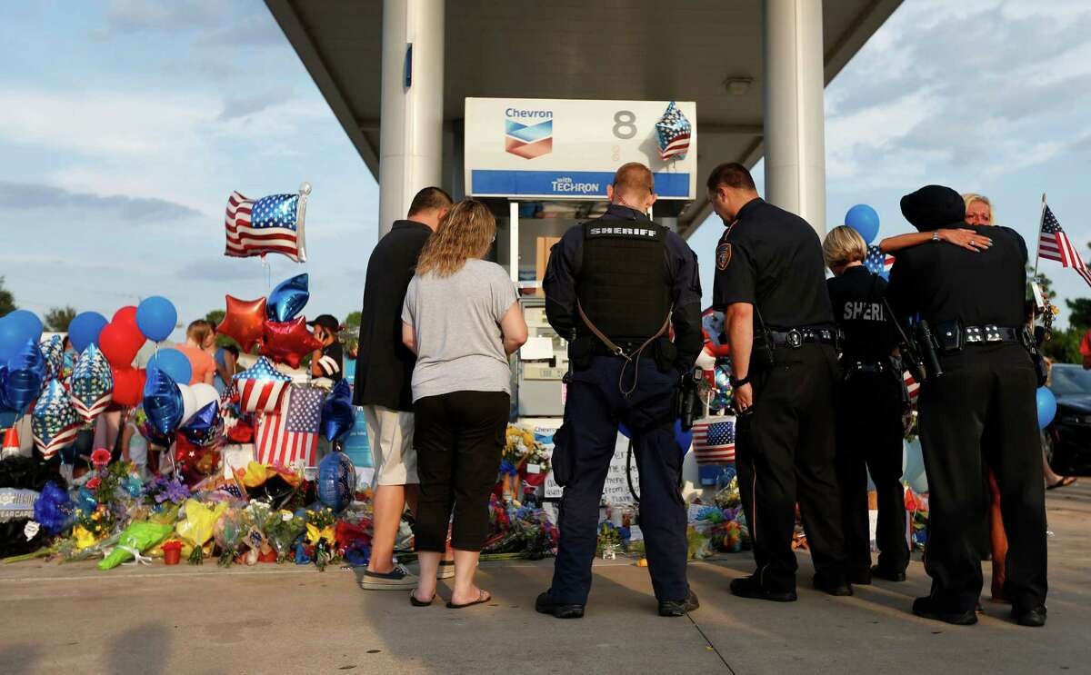 Harris County District 5 deputies hug and look at a growing memorial during a vigil Saturday held at the Chevron station where deputy Darren Goforth was shot and killed.