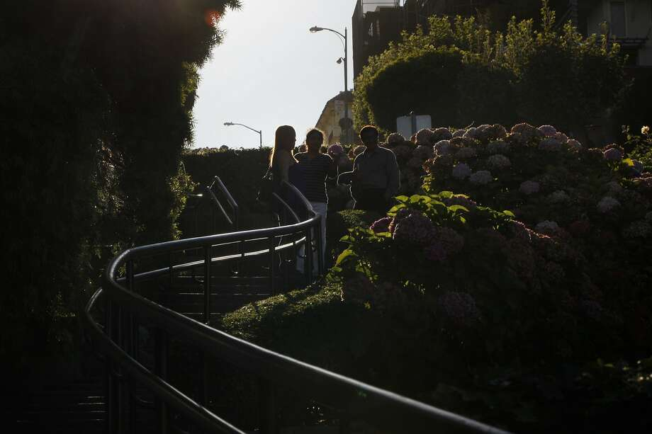 Tourists talk with each other on a landing on Lombard Street in San Francisco. Photo: Franchon Smith, The Chronicle