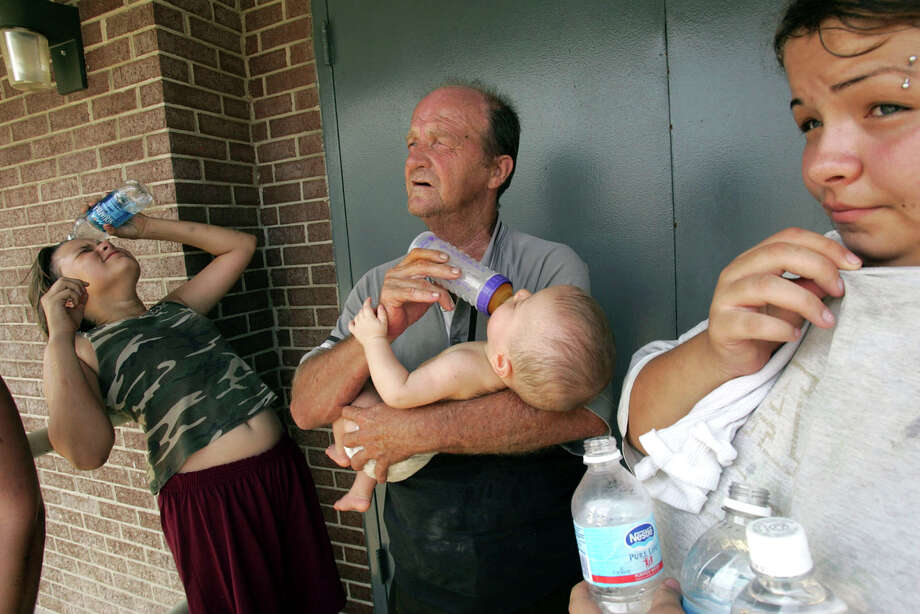 Cassondra Creed, 13, left, cools off while Ashley Vicknair, 18, right, stands with her grandfather, Douglas Adams, and her daughter, Selena Caillouet, 6 months, after they were rescued from St. Bernard Parish and taken by ferry to the Algiers Ferry Terminal across the Mississippi River from downtown New Orleans on Wednesday, August 31, 2005. Lisa Krantz/STAFF Photo: LISA KRANTZ, STAFF / SAN ANTONIO EXPRESS-NEWS / SAN ANTONIO EXPRESS-NEWS