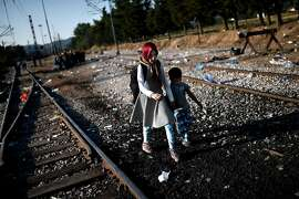 TOPSHOTS A young girl holds a young boy's hand as migrants walk on railway tracks to cross the border from Greece to Macedonia near the Greek village of Idomeni on August 29, 2015. The EU is grappling with an unprecedented influx of people fleeing war, repression and poverty in what the bloc has described as its worst refugee crisis in 50 years. AFP PHOTO / ARIS MESSINISARIS MESSINIS/AFP/Getty Images