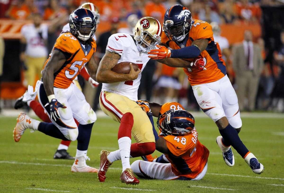 San Francisco 49ers quarterback Colin Kaepernick (7) is tackled by Denver Broncos' Shaquil Barrett (48), T.J. Ward (43) and Danny Trevathan.