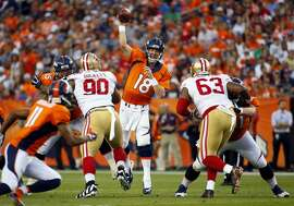 Denver Broncos quarterback Peyton Manning (18) throws as San Francisco 49ers defensive tackle Darnell Dockett (90) and Tony Jerod-Eddie (63) rush during the first half.