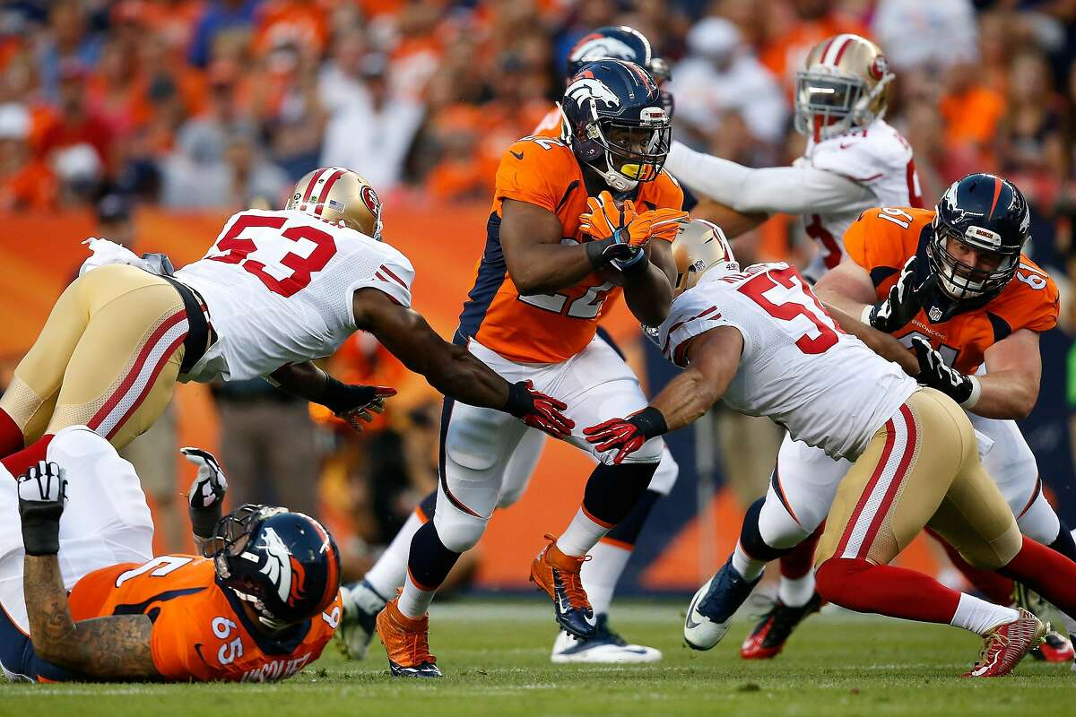 Running back C.J. Anderson #22 of the Denver Broncos breaks tackles by inside linebacker NaVorro Bowman #53 and inside linebacker Michael Wilhoite #57 of the San Francisco 49ers to rush for a first down during preseason action at Sports Authority Field at Mile High on August 29, 2015 in Denver, Colorado.