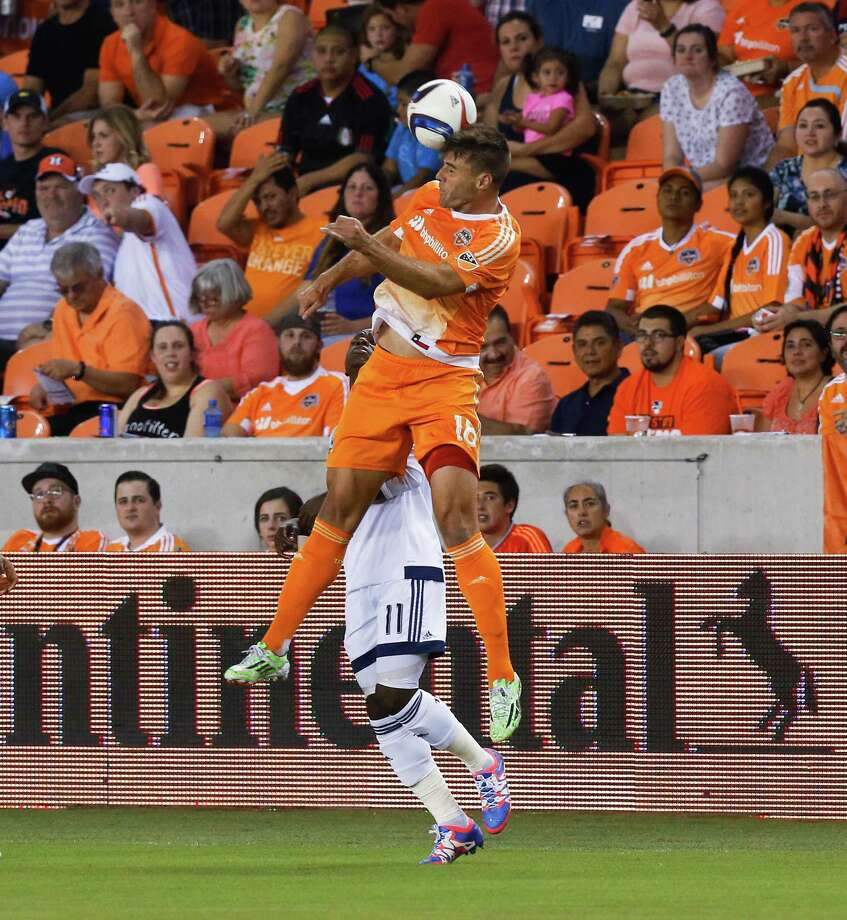 Houston Dynamo defender David Horst (18) heads the ball way from Vancouver Whitecaps forward Darren Mattocks (11) during the first half of an MLS soccer match Saturday, Aug. 29, 2015, in Houston. (AP Photo/Bob Levey) Photo: Bob Levey, FRE / FR156786 AP