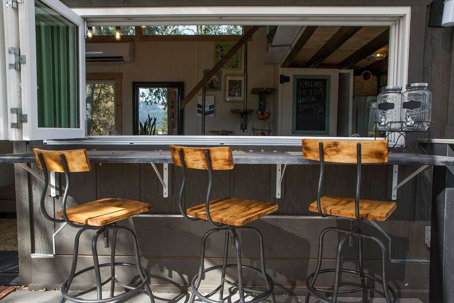 Joshua and Shelley Engberg's tiny house uses an accordion window to bridge outside and inside: The window opens onto an outside counter perfect for dining. Photo: Nathaniel Y. Downes, The Chronicle