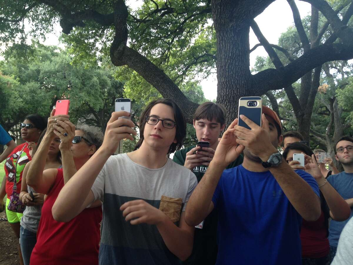 Xavier Rotnofsky (left) and other students ready their phones for the removal of the University of Texas at Austin's Jefferson Davis statue on Sunday, August 30, 2015.