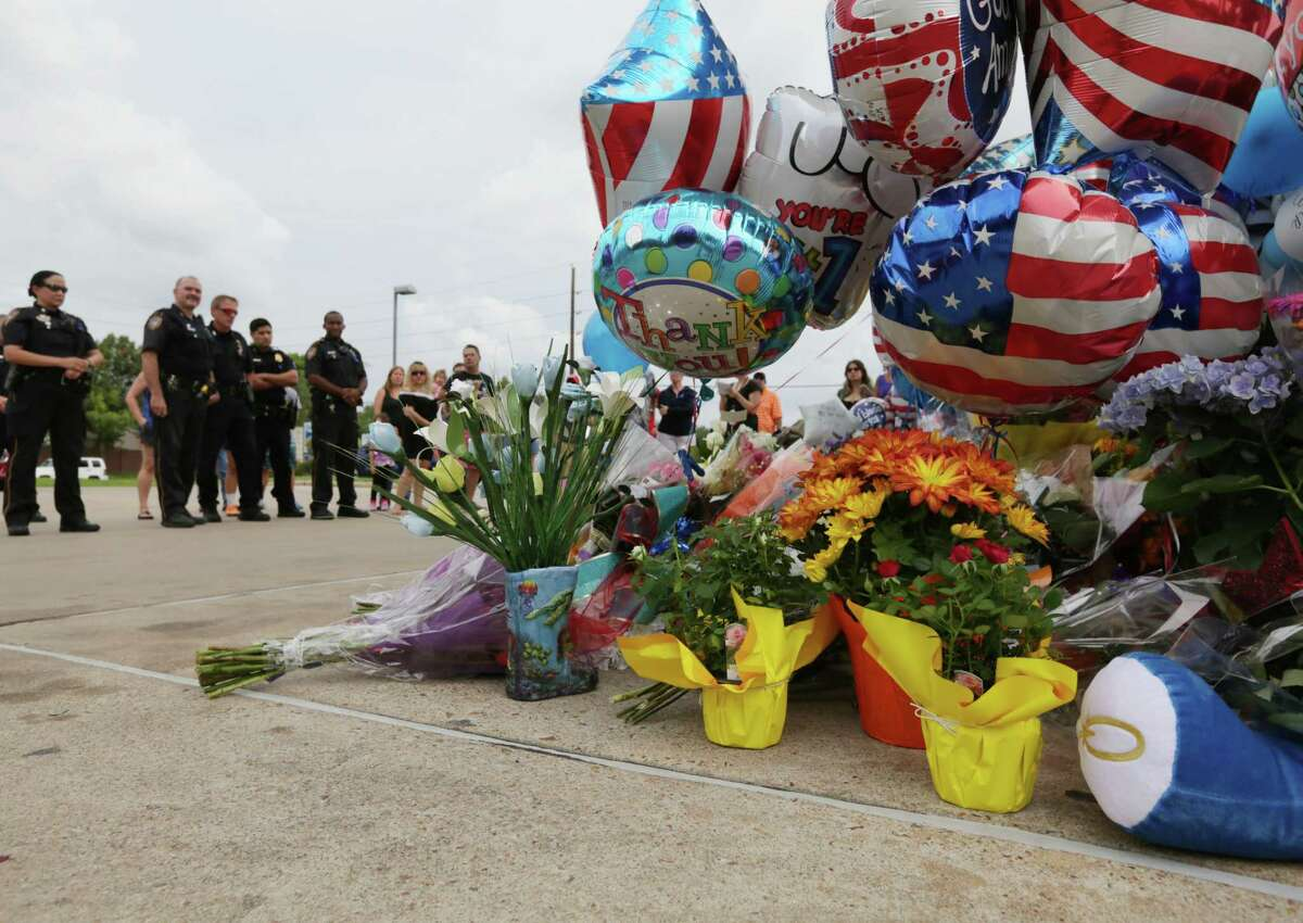 Mourners stand near a vigil for Harris County Sheriff's Deputy Darren Goforth, at the Chevron station where he was killed, Sunday, Aug. 30, 2015, in Houston.