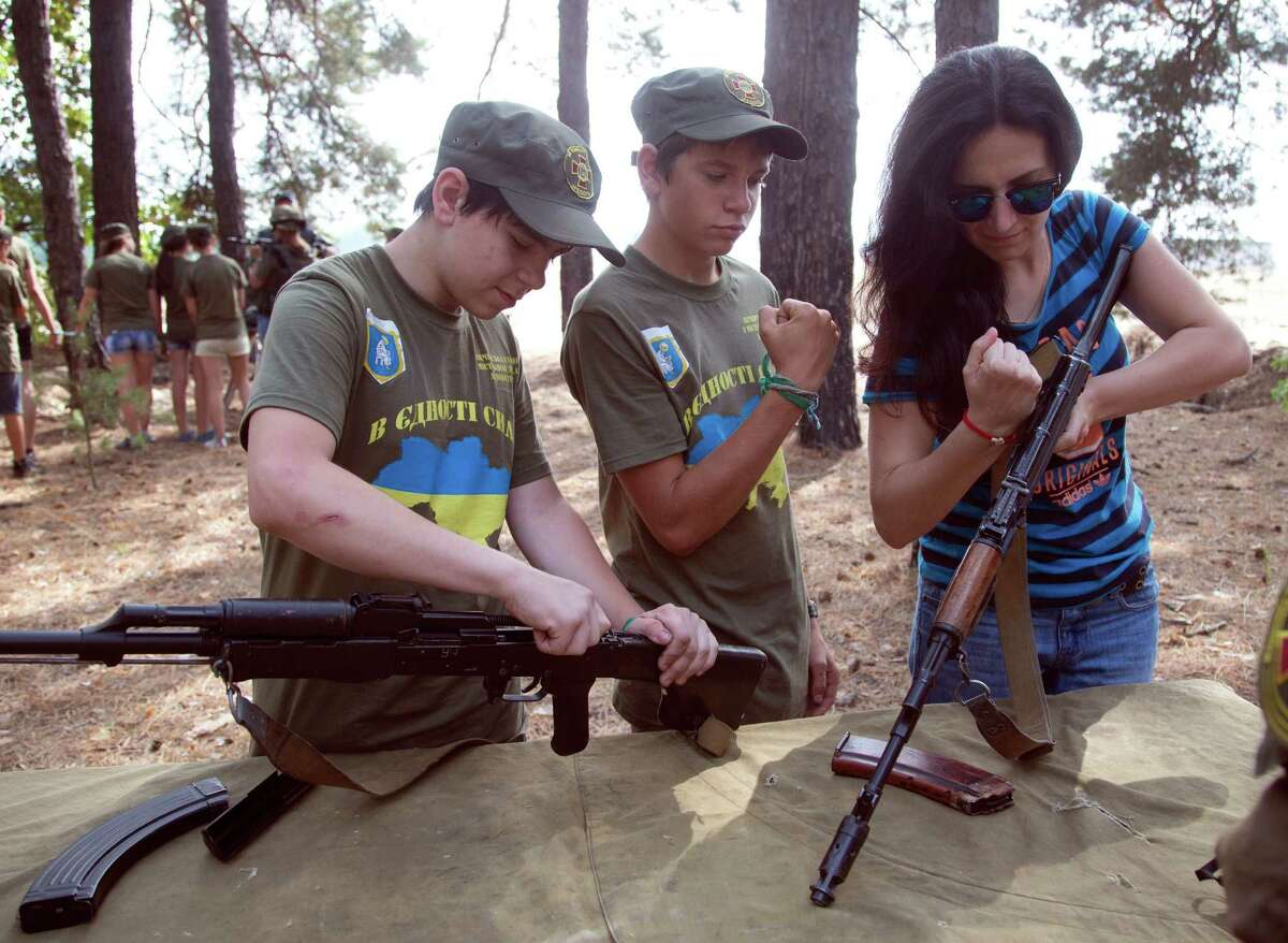 Teenagers and a school teacher try to dismantle machine guns at a military training ground of Ukraine's National Guard outside the village of Stare, the Kiev region, Ukraine, Saturday, Aug. 29, 2015.