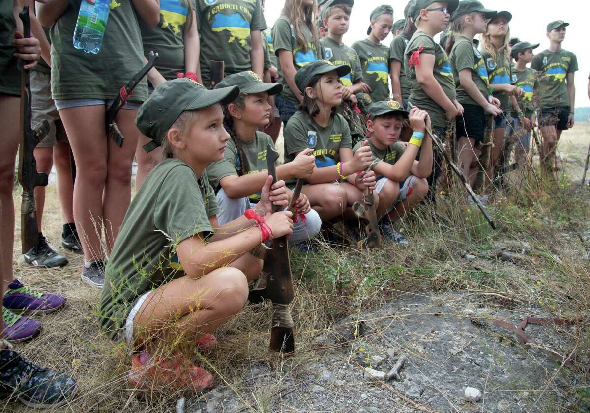 Children listen to instructors at a military training ground of Ukraine's National Guard outside the village of Stare, the Kiev region, Ukraine, Saturday, Aug. 29, 2015.