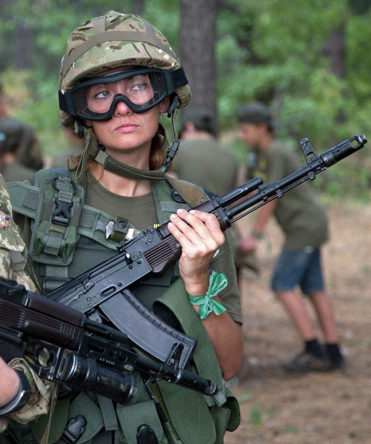 A school teacher in a military uniform watches as servicemen teach children to operate weapons at a military training ground of Ukraine's National Guard outside the village of Stare, the Kiev region, Ukraine, Saturday, Aug. 29, 2015.