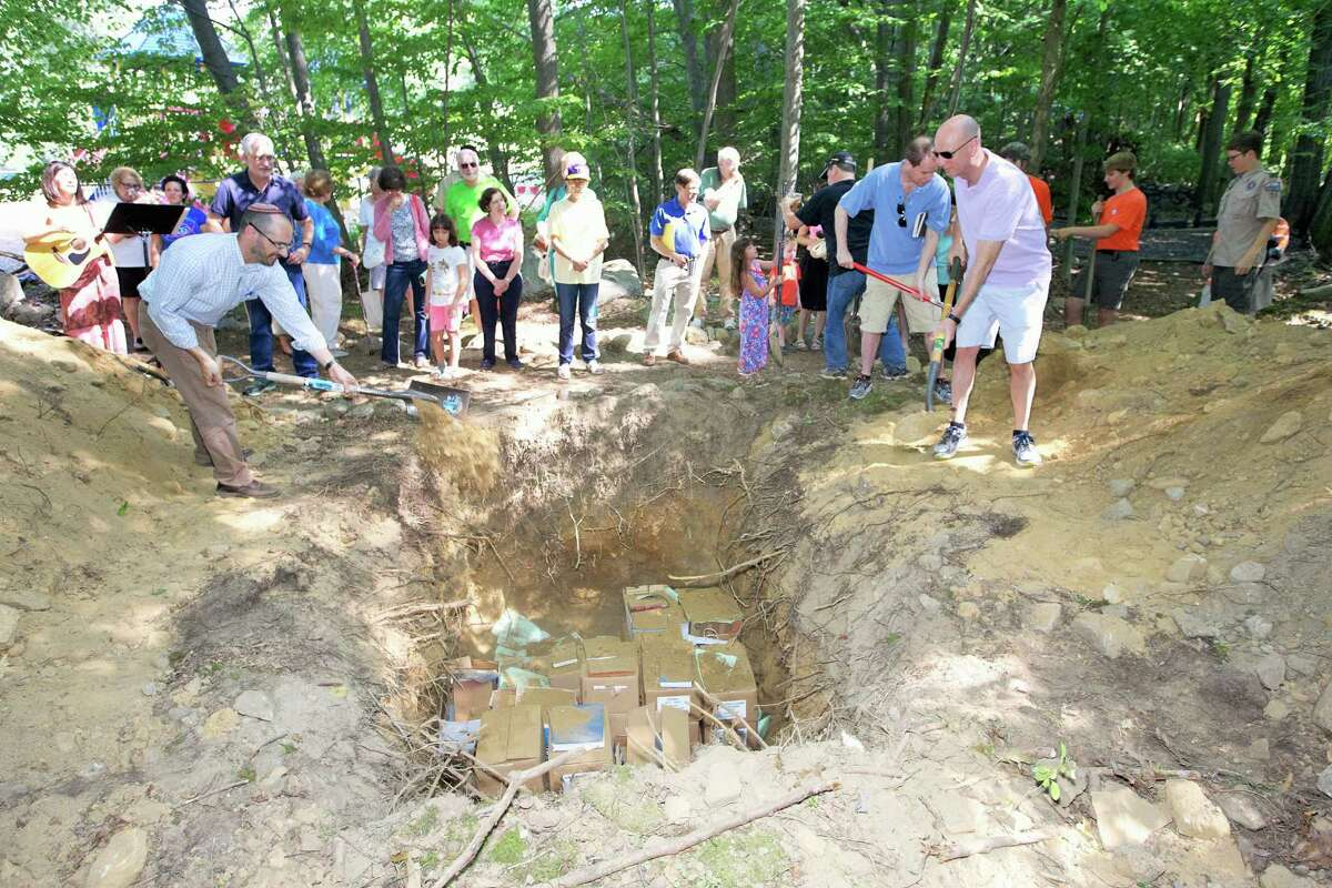 Congregants and members of BSA Troop 15 cover thousands of religious items in tomb in a burial grave site at the Temple Sinai in Stamford, Conn. on August 30, 2015.