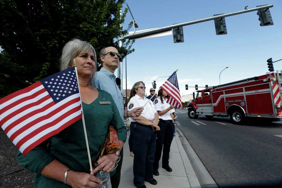 People watch as a motorcade headed to a memorial service for three firefighters killed in a wildfire passes, Sunday, Aug. 30, 2015, in Wenatchee, Wash. Richard Wheeler, Andrew Zajac and Thomas Zbyszewski died Aug. 19 in a fire near Twisp, Wash.