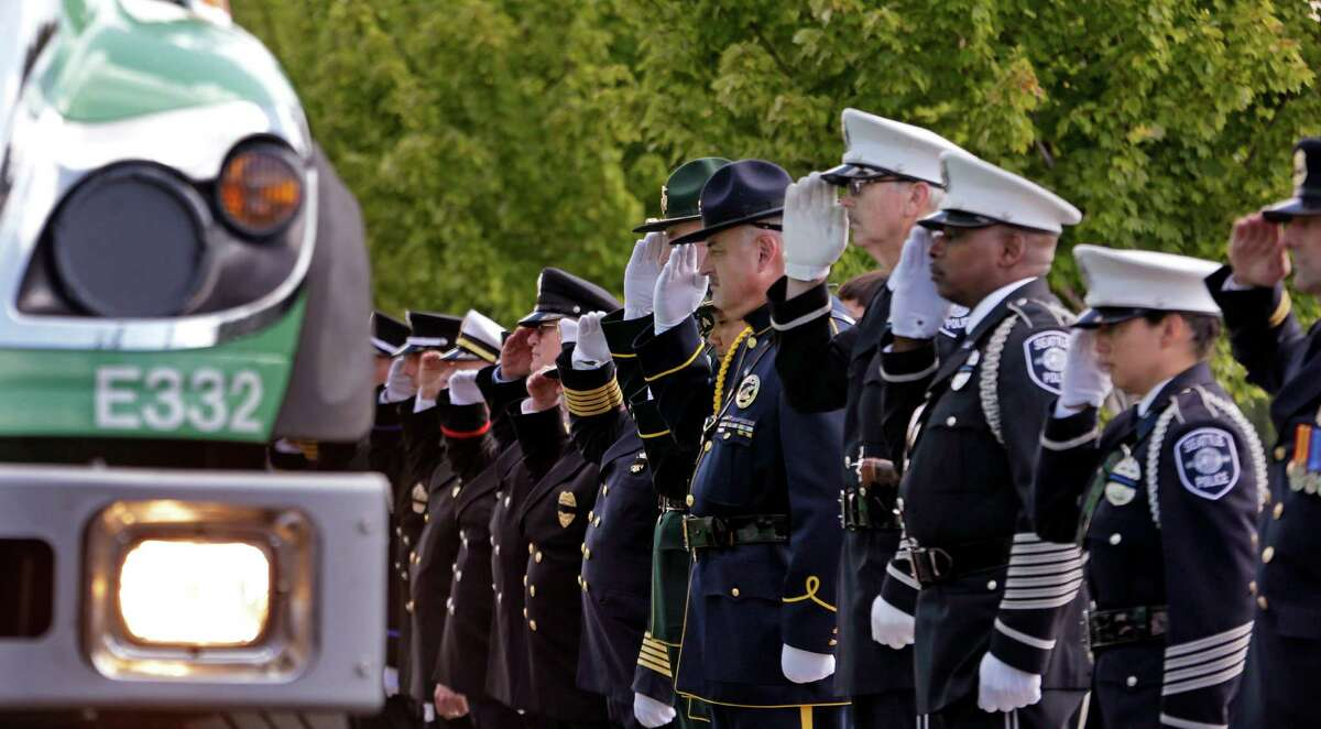 Firefighters salute as a U.S. Forest Service truck goes past before a memorial service for three firefighters killed in a wildfire, Sunday, Aug. 30, 2015, in Wenatchee, Wash. Richard Wheeler, Andrew Zajac and Thomas Zbyszewski died Aug. 19 in a fire near Twisp, Wash.