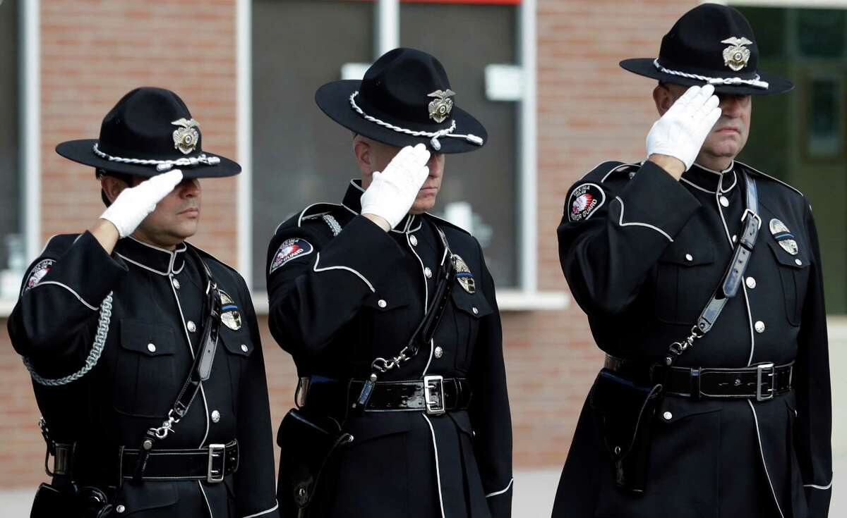Firerighters salute as a motorcade passes before a memorial service for three firefighters killed in a wildfire, Sunday, Aug. 30, 2015, in Wenatchee, Wash. Firefighters Richard Wheeler, Andrew Zajac and Thomas Zbyszewski died Aug. 19 in a fire near Twisp, Wash.