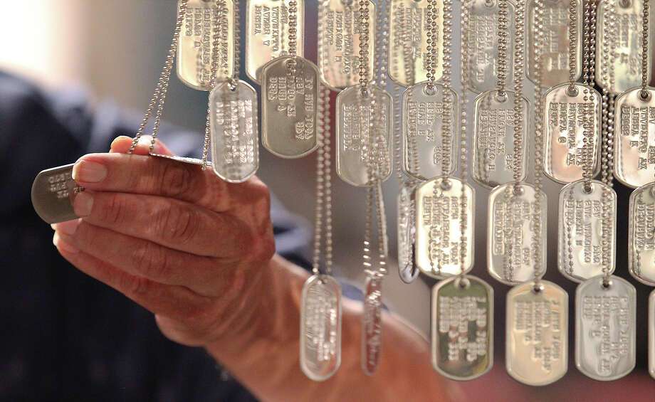 Jim Cisneros holds a dog tag  after a ceremony at the Institute of Texan Cultures for the Texas Vietnam Heroes exhibit on Aug. 3, 2013. The exhibit paid tribute to the 3,417 men who died in Vietnam with a collection of dog tags showing the names, military branch and the date of when the soldier was killed in action. Vietnam vets and family came to a special opening ceremony and some spent time finding their lost brethren after the ceremony. Photo: Kin Man Hui /San Antonio Express-News / ©2013 San Antonio Express-News