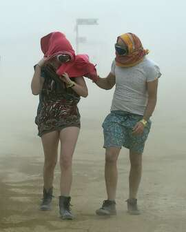 Robynne Rowlinson, left, and James Bisset, both from South Africa, walk through a morning dust storm at Burning Man on the Black Rock Desert in Gerlack, Nev. on Saturday, Aug. 29, 2015.  The 29th annual alternative living event traditionally centered around the ritual burning of a large wooden effigy (Andy Barron/The Reno Gazette-Journal via AP)  NO SALES; NEVADA APPEAL OUT; SOUTH RENO WEEKLY OUT; MANDATORY CREDIT