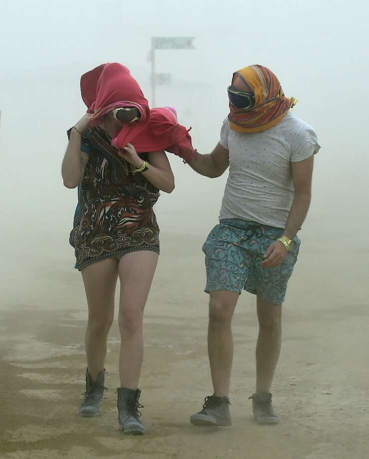 Robynne Rowlinson, left, and James Bisset, both from South Africa, walk through a morning dust storm at Burning Man on the Black Rock Desert in Gerlack, Nev. on Saturday, Aug. 29, 2015.  Photo: Andy Barron, Associated Press