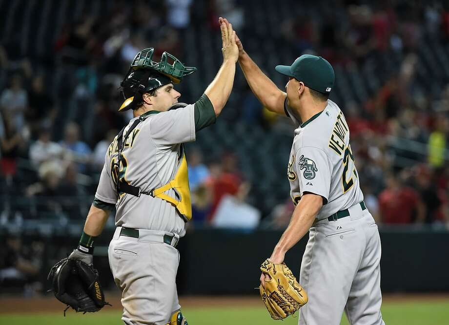 Pat Venditte #29 and Josh Phegley #19 of the Oakland Athletics celebrate a 7-4 win in eleven innings against the Arizona Diamondbacks at Chase Field on August 30, 2015 in Phoenix, Arizona.  Photo: Norm Hall, Getty Images