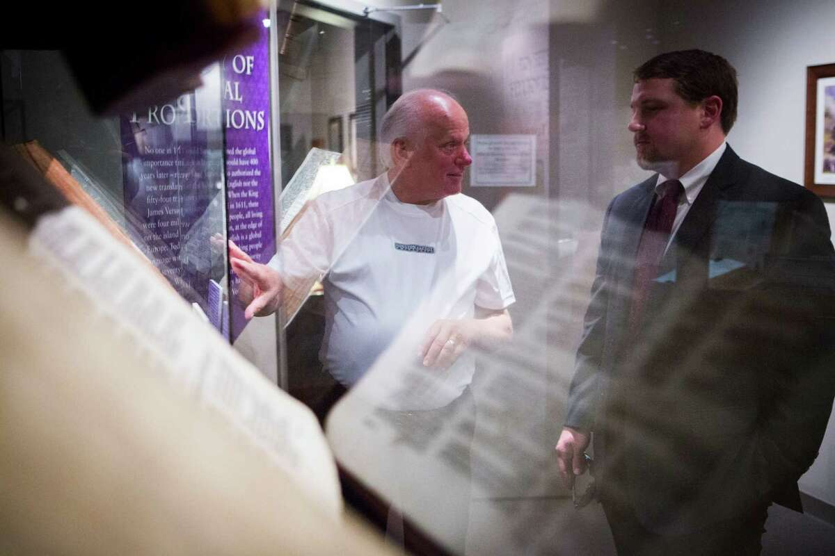 Rick Ogden, left, points out an exhibition to Kyle Vardeman at the Dunham Bible Museum. The Bibles displayed, translated by order of King James I, are among almost 6,000 writings shown there.