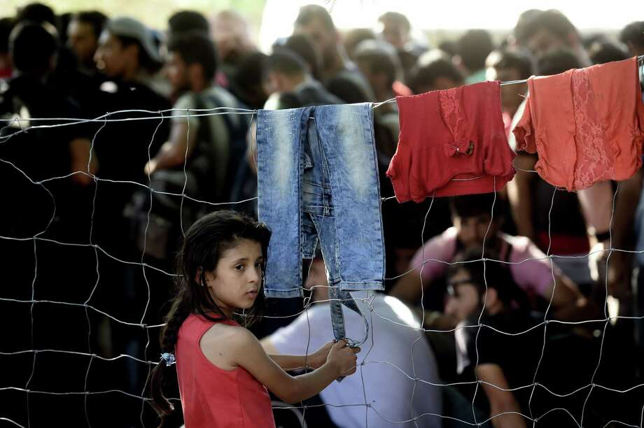 A girl stands at a fence near a registration camp in Presevo, Serbia, after the arrival of Syrian refugees. Photo: Aris Messinis /Getty Images / AFP