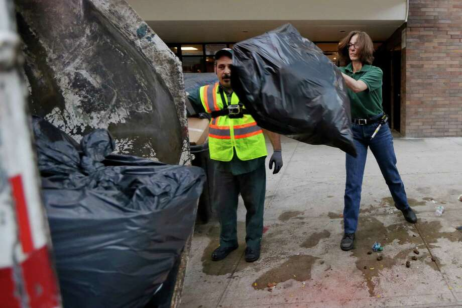 New York University professor and Department of Sanitation of New York anthropologist-in-residence Robin Nagle, right, tosses a bag of garbage into the truck as she accompanies sanitation worker Joe Damiano, during his morning rounds, Wednesday, Aug. 12, 2015, in New York. Nagle studies the refuse along the curbs of the nation's biggest city as a mirror into the lives of its 8.5 million residents. (AP Photo/Richard Drew) ORG XMIT: NYRD206 Photo: Richard Drew / AP