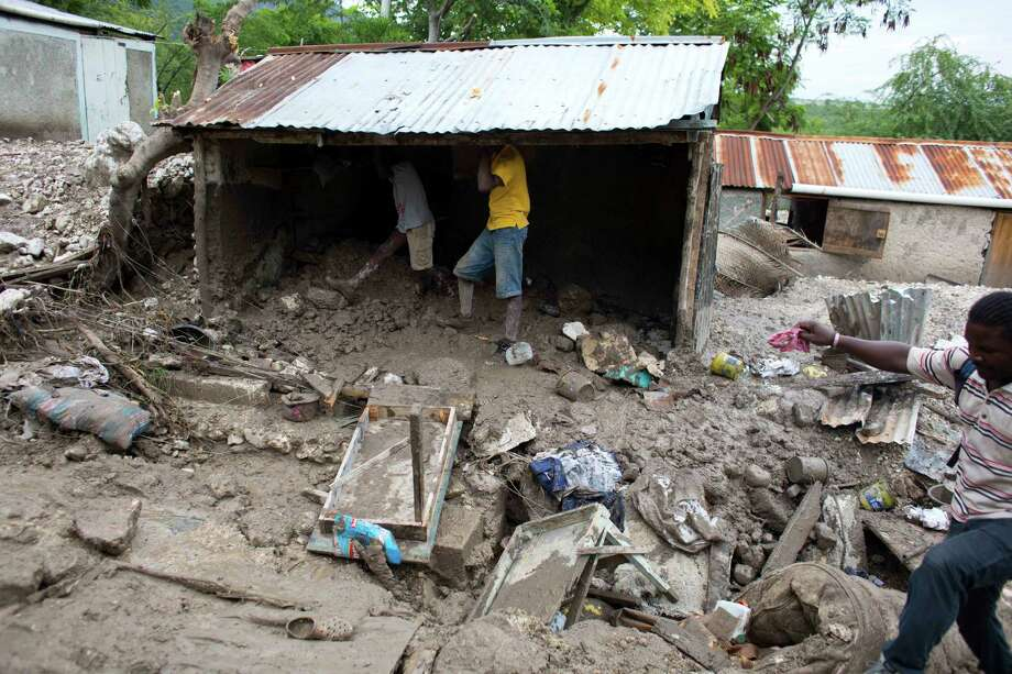 Residents salvage personal items after a mudslide triggered by Tropical Storm Erika left it partially submerged, in Montrouis, Haiti, Saturday, Aug. 29, 2015. Erika dissipated early Saturday, but it left devastation in its path on the small eastern Caribbean island of Dominica, and parts of Haiti, authorities said. (AP Photo/Dieu Nalio Chery) ORG XMIT: DC125 Photo: Dieu Nalio Chery / AP